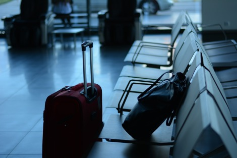 Maletas en un aeropuerto y viajeros esperando